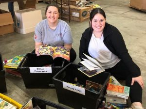 Two VISTA members sorting through boxes of children's books.