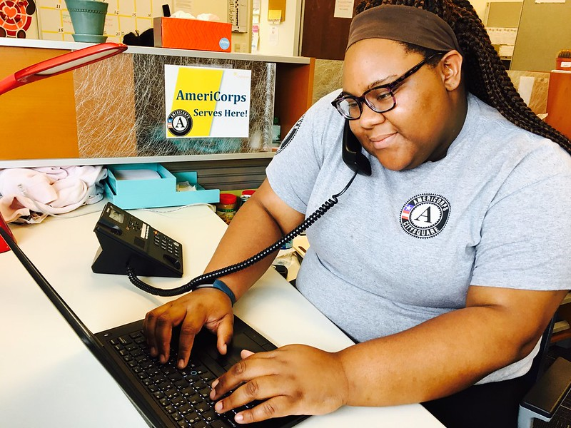 AmeriCorps members on the phone while typing on a laptop.