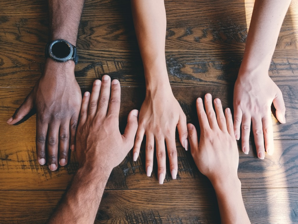 Human hands of varying skin tone resting on a wooden table