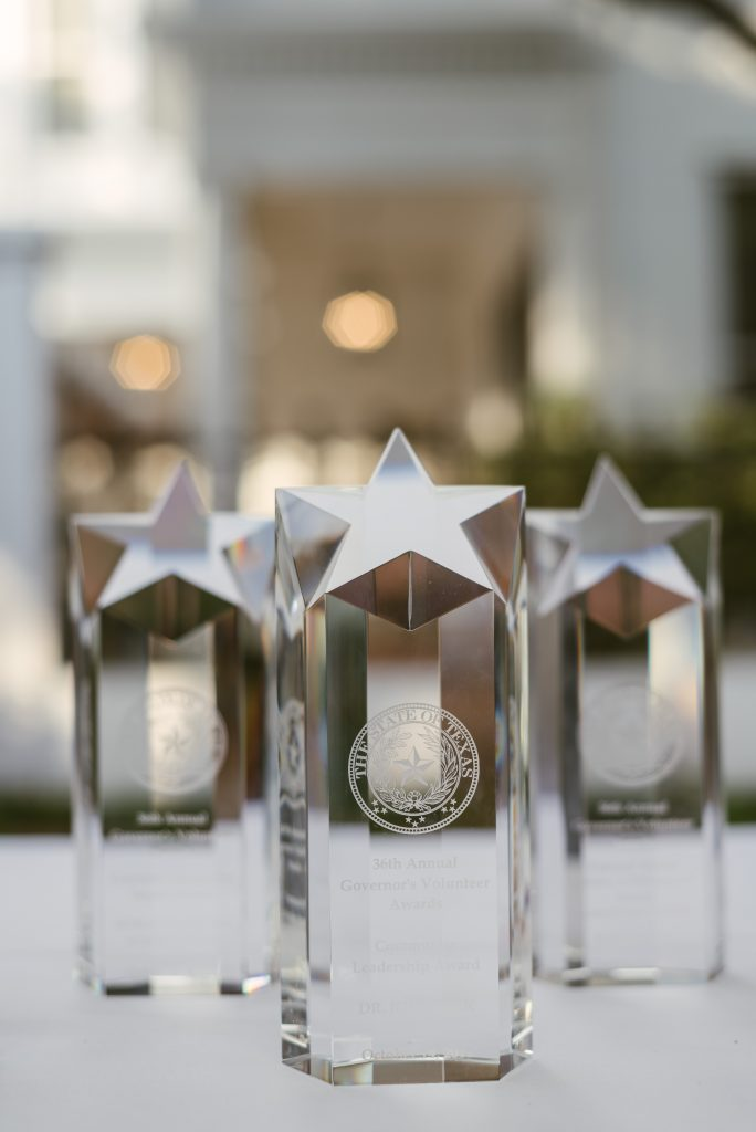Three glass Governor's Volunteer Award trophies lined up on a white tablecloth.