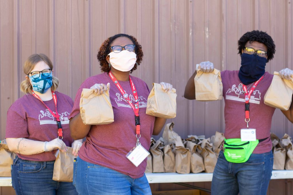 Three AmeriCorps members wearing cloth facemasks hold up brown bags during a meal distribution.